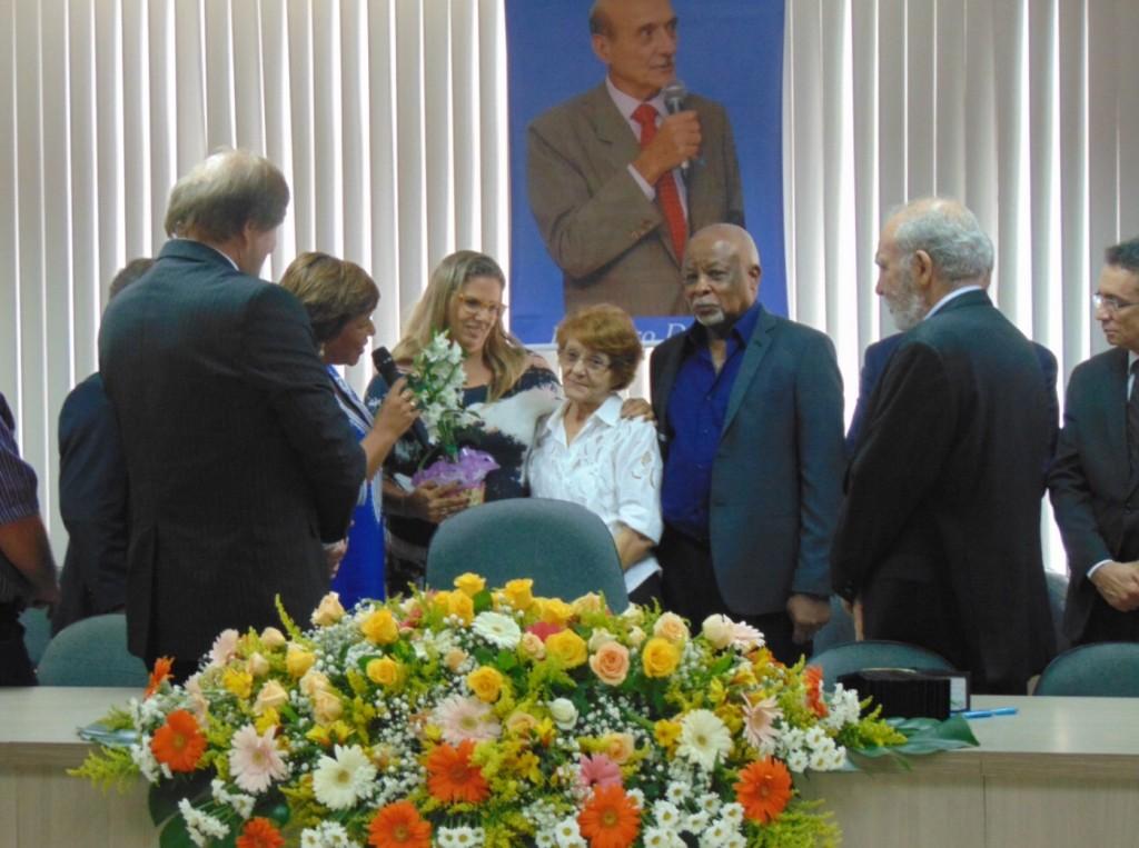Maria Glória Dominguez recebe a homenagem das mãos de Clarissa Costa